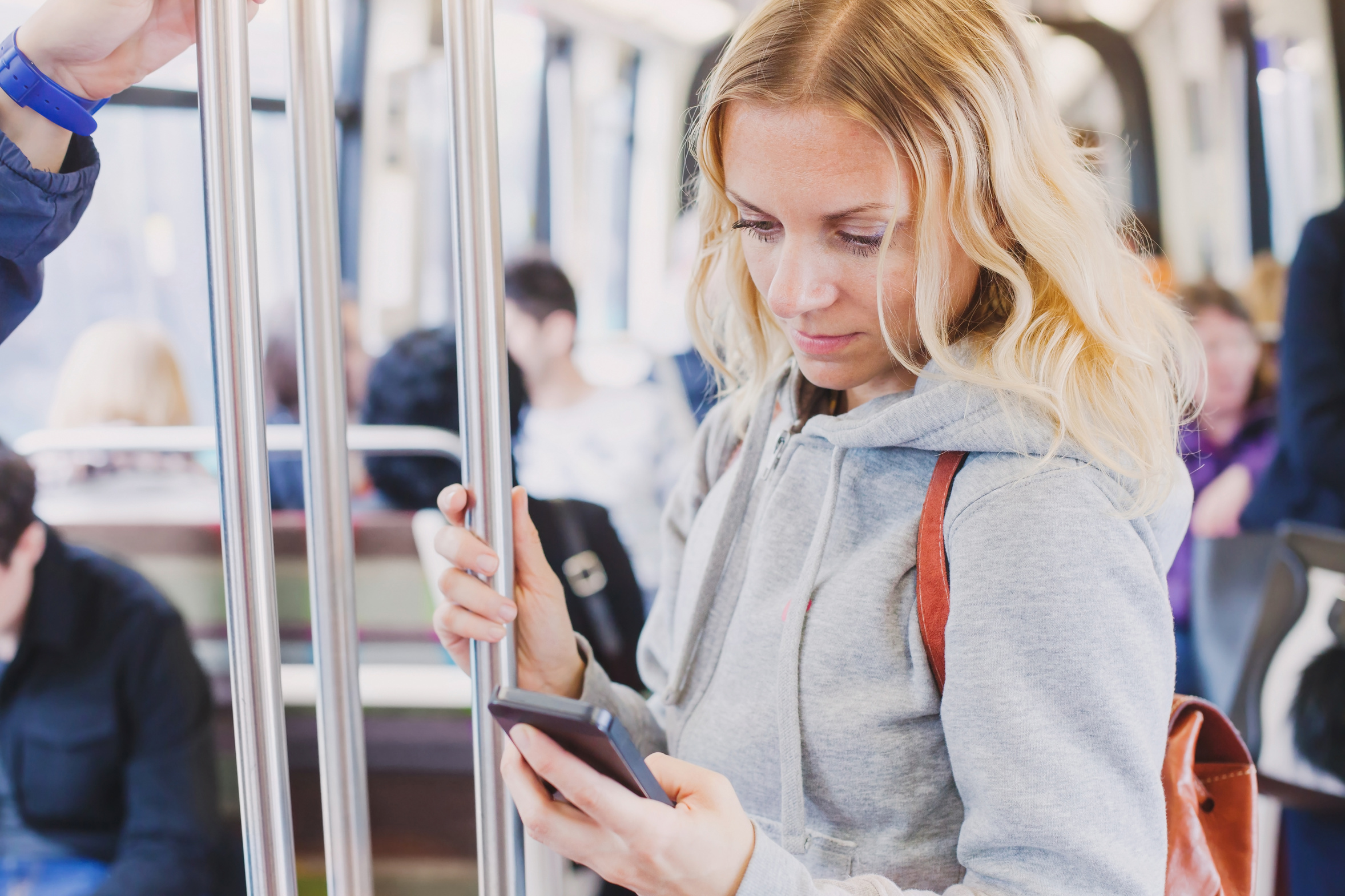 people in metro, commuters, woman passenger looking at the screen of her smartphone
